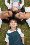 Lively family lying in a circle on the grass. In a park Stock Image