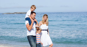 Lively family walking on the sand Stock Image