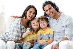 Lively family watching TV together stock image