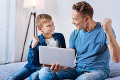 Lively father and son celebrating victory while watching football online. Happy fans. Upbeat young father and son sitting on the bed and watching football online Royalty Free Stock Image