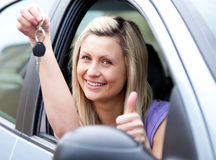 Lively female driver showing a key. With a thumb up after buying a new car stock photo