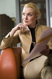 Lively interest. Elegant blond woman in goldish trouser suit sitting on comfortable orange chair showing notes Stock Photos
