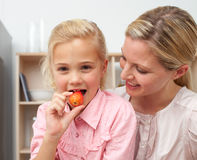 Lively little girl eating fruit with her mother Royalty Free Stock Image
