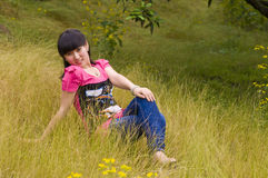 Lively and playful girl in citrus orchard. A Lively and playful chinese girl was sitting in the citrus orchard which with full of yellow weeds stock photos