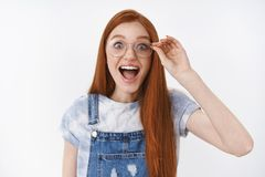 Lively redhead impressed happy girl wear denim overalls smiling amazed cheerful touch glasses look camera astonished and. Pleased, express amazement and joy of stock image