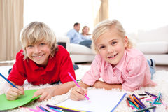 Lively siblings drawing lying on the floor Royalty Free Stock Photos