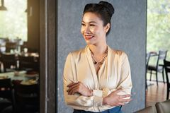 Lively smiling Asian female standing in cafe royalty free stock photo
