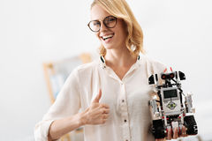 Lively woman demonstrating digital little robot indoors Royalty Free Stock Photo
