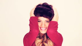 Lively Woman In Fur Hat. With her hands to the earflaps laughing at the camera stock video footage