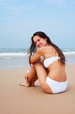 Lively woman sitting on the sand. Lively woman in white bikini sitting on the sand Royalty Free Stock Photo