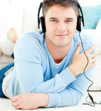 Lively young man listen to music with headphones. In the living room Stock Photo