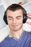 Lively young man listening to music on the couch Royalty Free Stock Photos
