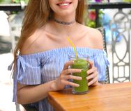 Lively young woman drinking fresh smoothie. In cafe Royalty Free Stock Image
