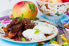 Liver with apples in red wine sauce with rice garnish Stock Photography