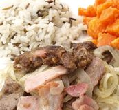 Liver dish. Liver with bacon, wild rice, carrots and onion meal stock photography