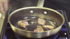 The liver frying on the pan. Cooking in the restaurant. The liver frying on the pan. Close up hands of the chef turning it from side to side stock video