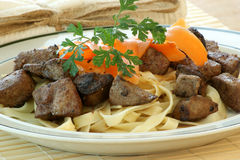 Liver goulash on pasta with carrot Stock Images