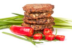 Liver pancakes or cutlets with chili pepper and green onions iso. Lated on white background Royalty Free Stock Image