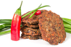Liver pancakes or cutlets with chili pepper and green onions  on white background.  Royalty Free Stock Photography