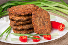 Liver pancakes or cutlets with chili pepper and green onions on a wooden background.  Royalty Free Stock Photo