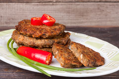 Liver pancakes or cutlets with chili pepper and green onions on a wooden background.  Stock Photos