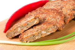 Liver pancakes or cutlets with chilli and spring onions on a cutting board close-up isolated white background. Liver pancakes or cutlets with chilli and spring Royalty Free Stock Photography