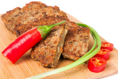 Liver pancakes or cutlets with chilli and spring onions on a cutting board close-up  white background. Liver pancakes or cutlets with chilli and spring onions on Stock Photo