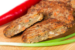 Liver pancakes or cutlets with chilli and spring onions on a cutting board close-up  white background. Liver pancakes or cutlets with chilli and spring onions on Stock Image