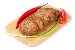 Liver pancakes or cutlets with chilli and spring onions on a cutting board isolated white background. Liver pancakes or cutlets with chilli and spring onions on Royalty Free Stock Photos