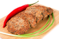 Liver pancakes or cutlets with chilli and spring onions on a cutting board isolated white background. Liver pancakes or cutlets with chilli and spring onions on Royalty Free Stock Image