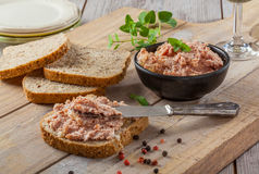 Liver pate and bread. Delicious liver pate meat spread on whole wheat bread. Rustic wooden cutting board and table royalty free stock photo
