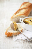 Liver pate on a spoon on slice of baguette. Liver pate on a slice of baguette Royalty Free Stock Photo