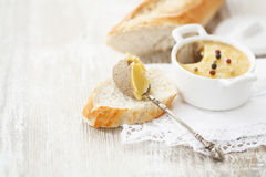 Liver pate on a spoon on a slice of baguette. Liver pate on a slice of baguette Stock Images