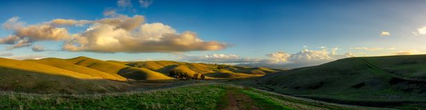Livermore Brushy Peak Regional Reserve. Green valley hills with sunset over the horizon on the right. Clouds and blue sky, with some stars visible Royalty Free Stock Photos