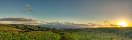 Livermore Brushy Peak Regional Reserve. Green valley hills with sunset over the horizon on the right. Clouds and blue sky, with some stars visible stock photo