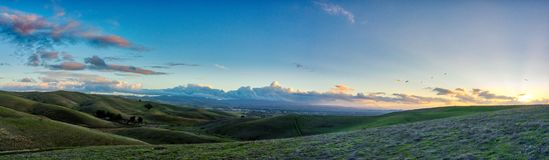 Livermore Brushy Peak Regional Reserve. Green valley hills with sunset over the horizon on the right. Clouds and blue sky, with some stars visible Stock Photography