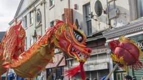 Liverpool-Chinesisches Neujahrsfest - anstarrend Sie aus- Dragon Dancers auf den Straßen von Liverpool Stockbild