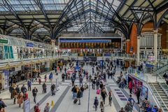 View of Liverpool Street mainline station. Liverpool Street, London, UK - April 6, 2018: View of concourse and departure board with lots of people travelling Royalty Free Stock Images