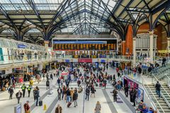 Inside Liverpool Street Station. Liverpool Street, London, UK - April 6, 2018: wide angle shot of a busy mainline station with lots of passengers. Well lit view Royalty Free Stock Photo