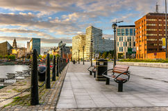 Liverpool Waterfront at Sunset. Pedestrian Fottopath, lined with benches and street lights, along the waterfront of Liverpool Royalty Free Stock Images