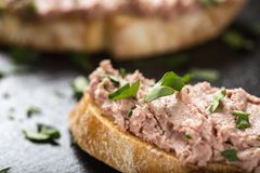Liverwurst Sandwich with chopped parsley on a dark slate. Close up view Stock Images
