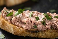 Liverwurst Sandwich with chopped parsley on a dark slate. Close up view Stock Photo