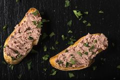 Liverwurst Sandwich with chopped parsley on a dark slate. Top view Royalty Free Stock Photo