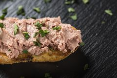 Liverwurst Sandwich with chopped parsley on a dark slate - close. Liverwurst Sandwich with chopped parsley on a dark slate - top view Stock Photos