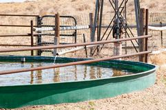 Livestock water tank supplied by a windmill royalty free stock image