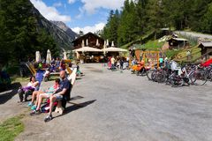 People sunbathing in front of restaurant with playing kids and bikes on bank of Lago di Livigno in Livigno, Italy. LIVIGNO, ITALY - AUGUST 1: People sunbathing royalty free stock image