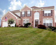 Living The American Dream. Beautiful Home in the Suburbs - Large two story brick house with a spacious front lawn and beautiful landscaping sits up on a hill in stock images
