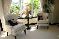 Living area with view of garden. Bright area of living room, showing two club chairs and a view of the garden stock photos