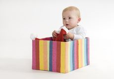 Living in a box. Young boy sitting in a coloured cardboard box Stock Images