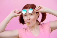 Living on bright side of life: portrait of beautiful woman in pink shirt with pigtails hairstyle, blue sunglasses and lollipop royalty free stock image